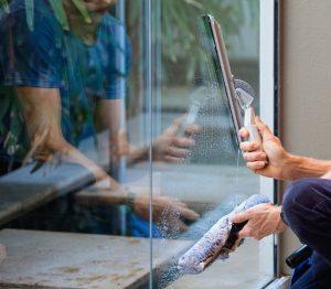 man som putsar fönster med fönsterskrapa och tvättpäls
