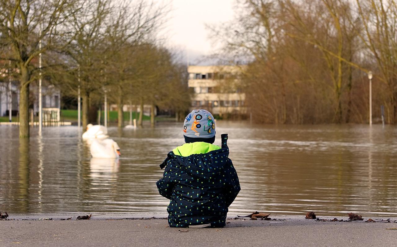 flicka tittar ut på översvämmad yta. Hydraosäckar kan stoppa vattenflöden