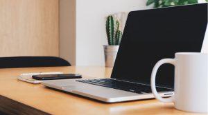 Skrivbord med dator, telefon och kaffekopp