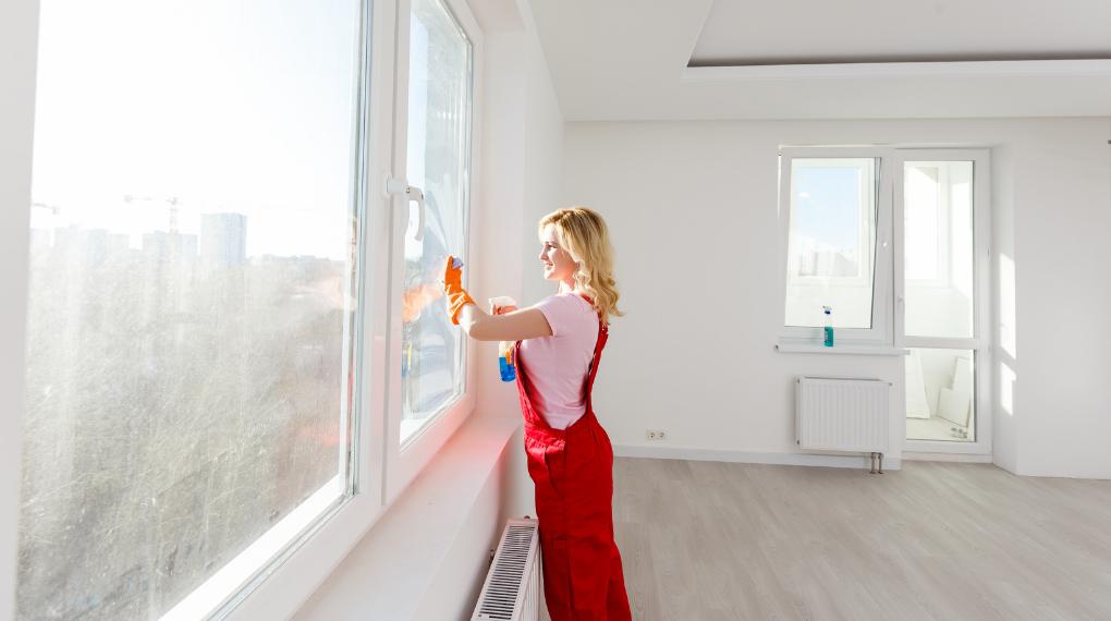 kvinna i röda byxor rengör fönster med luddfria trasor och fönsterputsmedel