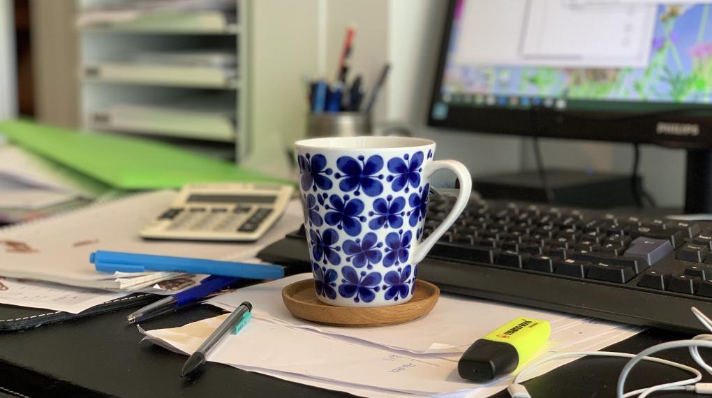 Kaffekopp på ett stökigt skrivbord